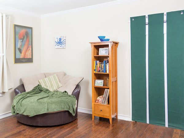 acoustidoor shown in hunter green with white straps is a sound-blocking door panel - shown unbuckled and rolled down - Residential Acoustics